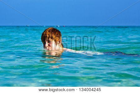 Boy Enjoys The Beautiful Clean Sea And Has Fun