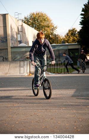 Joung Red Haired Boy Jumps With His Bmx Bike At The Skate Park