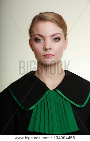 Law court or justice concept. Portrait young woman lawyer attorney wearing polish Poland black green gown on gray