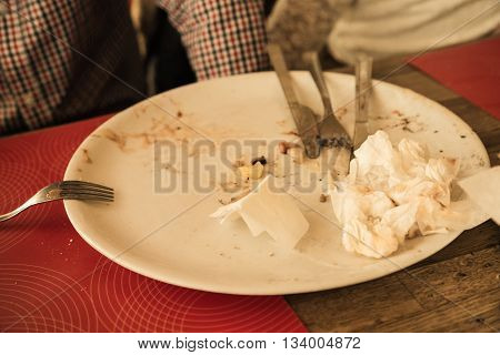 Food leftovers. Dirty plate and cutlery after the meal is finished.
