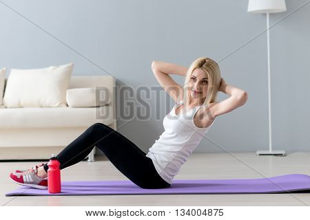 Pretty sporty girl is doing sit-ups. She is sitting on carpet in her living room and smiling. The lady is raising arms behind head