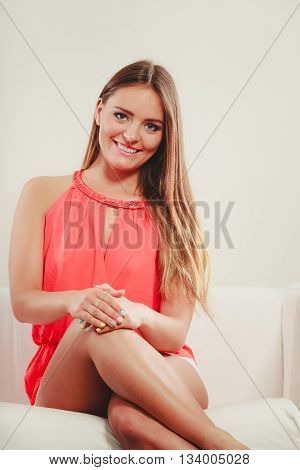 Portrait of cute attractive young woman girl in red shirt on sofa couch. Summer female fashion vogue.