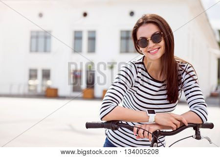 Just smile. Sincere young woman with sunglasses posing hands on the handle bar of a bike and looking at the camera