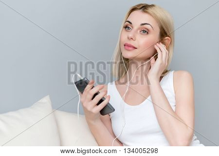Attractive young woman is enjoying music at home with pleasure. She is sitting on sofa and relaxing. The lady is holding a mobile phone and touching headphones