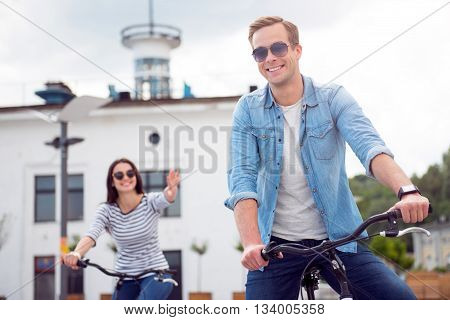 A little competition. Joyful smiling young man with sunglasses sitting on the bike with woman riding to him on the background