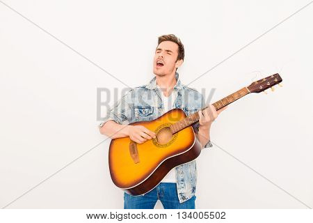 Young musician playing on guitar and singing on white background