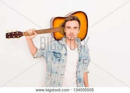 Portrait of handsome young man holding his guitar on shoulders