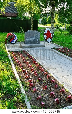 VELIKY NOVGOROD RUSSIA - MAY 29 2016. Memorial stone set on the spot of death of fighters of 3rd Armored Division in August 1941 decored with memorial wreaths