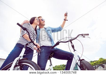 Say cheese. Beautiful young woman and joyful young man sitting on the bikes and looking at the phone while making a selfie
