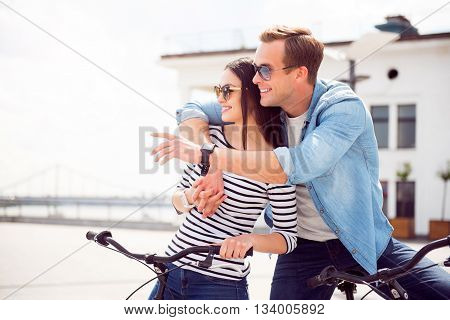 It is interesting. Delighted smiling guy hugging a charming woman and they looking at the same direction while sitting on the bicycles