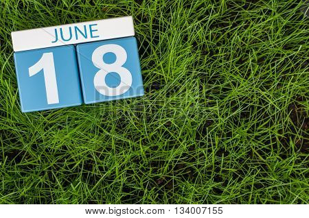 June 18th. Image of june 18 wooden color calendar on greengrass lawn background. Summer day, empty space for text.