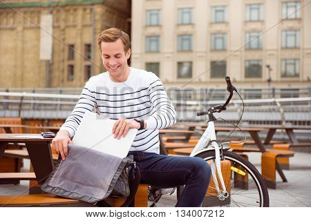 Working on the open air. Confident smiling young man taking out of a bag his laptop while sitting at the cafe near a bike