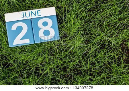 June 28th. Image of june 28 wooden color calendar on greengrass lawn background. Summer day, empty space for text.