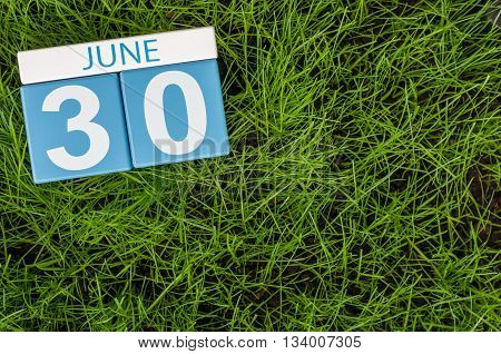 June 30th. Image of june 30 wooden color calendar on greengrass lawn background. Summer day, empty space for text.