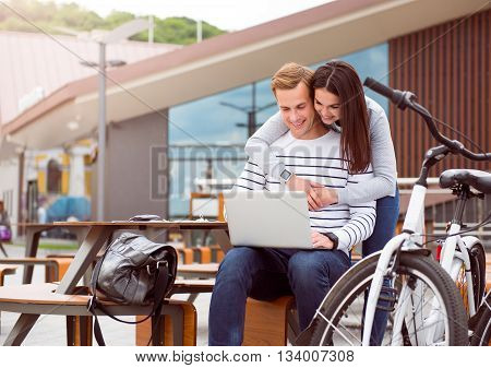 Nice time. Pretty young woman hugging a handsome man who tapping on the laptop while sitting at the table