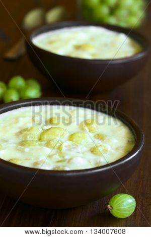 Traditional Hungarian Piszkeszosz or Piszkemartas a cooked gooseberry milk and egg dessert served in rustic bowls photographed on dark wood with natural light (Selective Focus Focus in the middle of the first bowl)