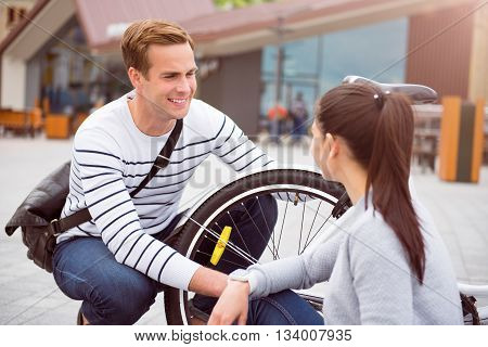Smile to her. A young handsome guy looking with interest at a pretty woman while squatting near a bike