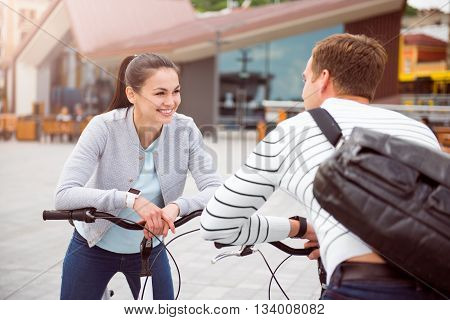 Warm look. Smiling pretty woman and handsome man looking at each other while leaning on their bikes