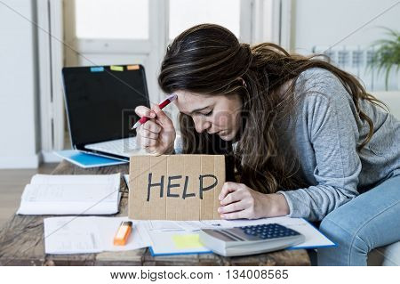 young woman asking for help suffering stress doing domestic accounting paperwork bills and invoices worried and stressed at home sofa couch with laptop computer calculator and bank receipts