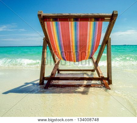 wooden chair at the beach with clear view to empty beach - symbol