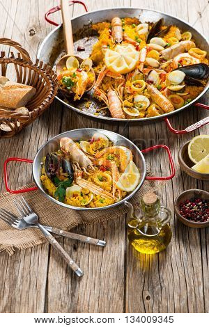 Typical spanish paella with seafood in a paelleras on a old rustic wooden table.