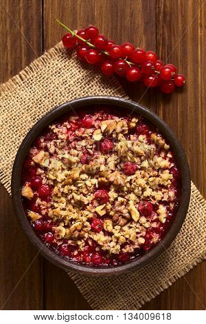 Redcurrant crumble or crisp with oatmeal and walnut on top baked in rustic bowl photographed overhead on dark wood with natural light (Selective Focus Focus on the top of the crumble)