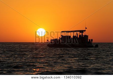 Ferry boat sunset is a boat full of passengers watching the beutiful sun as it sets on the ocean horizon.