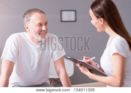 In a good mood. Smiling and merry female physiotherapist asking about health a patient sitting in the medical office