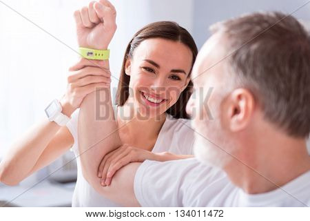 More exercises. Smiling and merry young female physiotherapist examining her male patient hand in a medical office