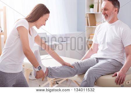 Eldercare. Smiling and positive young female physiotherapist stretching her male patient leg in a medical office