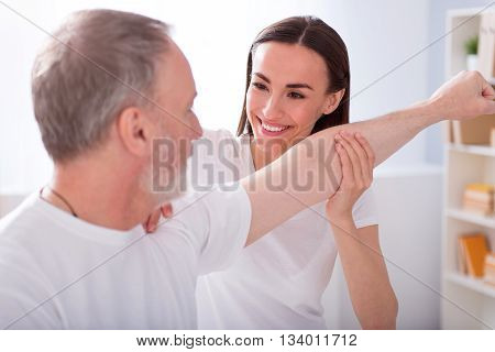 Nursing assistance. Smiling and delighted physiotherapist examining a man's hand in the medical office