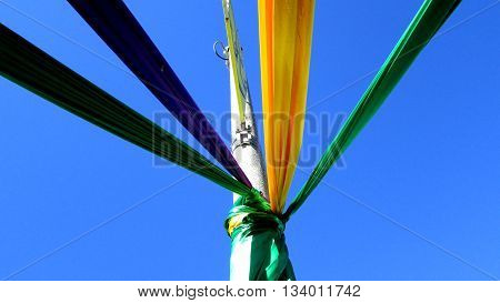 Colorful fabric streamers in the traditional Mardi Gras colors are tied to a post.