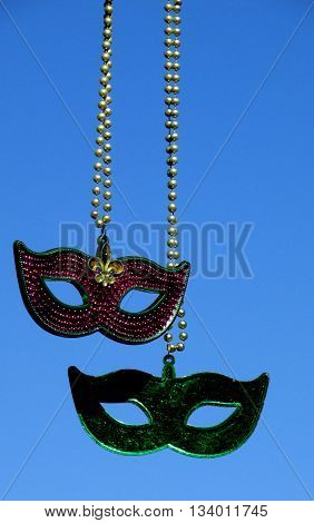 A pair of Mardi Gras masks dangle freely.