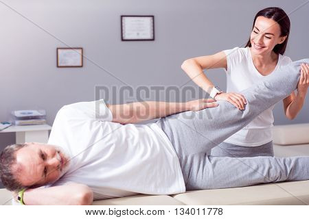 Healing. Cheerful male patient lying down with female smiling and merry physiotherapist performing some stretch exercises on mans leg