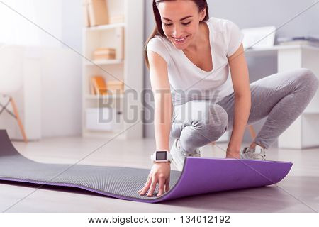 Rehab equipment. Cheerful and positive female physiotherapist using a mat