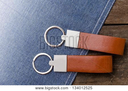 Leather Key Chain With Blue Fabric On Wooden Background
