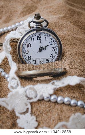 Vintage pocket watch drop on sand background