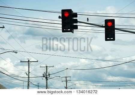 traffic light and street power poles against cloudy sky