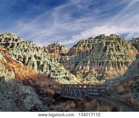 Multicolored and worn hills tower over a bridge in Eastern Oregon.