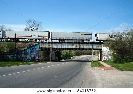 JOLIET, ILLINOIS / UNITED STATES - MAY 3, 2015: A freight train crosses a bridge over Ruby Street near downtown Joliet, Illinois.