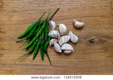 gralic and green chilli on wooden background