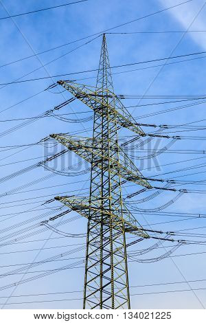 tower for electricity in rural landscape under blue sky