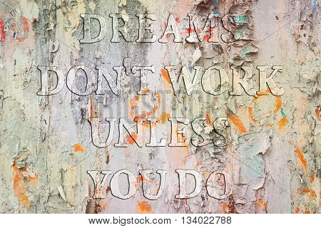 Dreams don't work until you do. Motivational quote about success and self actualization. Uneven transparent protuberant font on a grunge wall background.