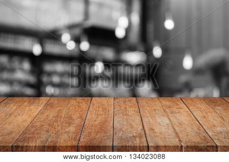 Wooden tabletop with black and white coffee shop blurred background, stock photo