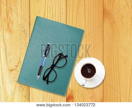 Notebook with office supplies with pen with glasses and cup of coffee on wood background