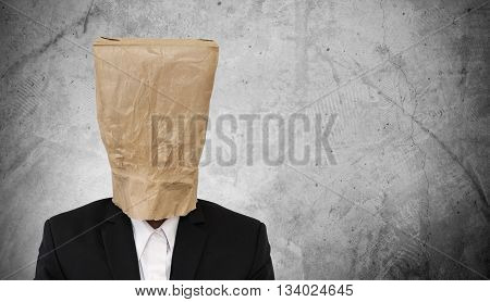 Businessman with brown paper bag on head, on dark concrete texture background, with copy space