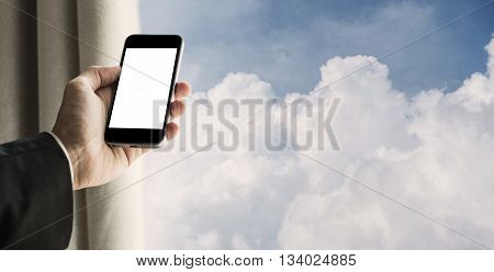 Businessman using mobile phone with curtain opened, and blue sky with fluffy clouds background