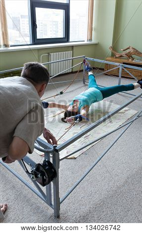 Old Russian collapsible simulator algorithm straightening the spine, and muscle tension. Pilates instructor doing exercises. Young woman locked in the simulator room for treatment. for stretching equipment. The concept of learning and improvement.