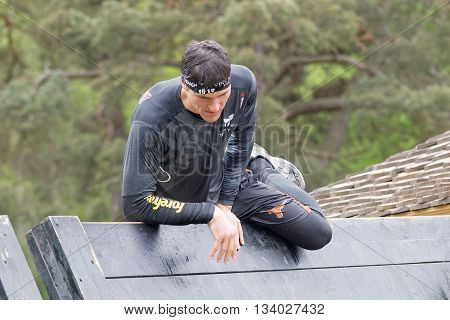 STOCKHOLM SWEDEN - MAY 14 2016: Man climbing over a plank obstracle in the obstacle race Tough Viking Event in Sweden May 14 2016