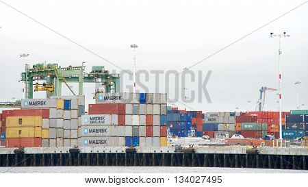 Oakland CA - June 07 2016: Hundreds of shipping containers line the docks at the Port of Oakland Middle Harbor. Sea transport has been the largest carrier of freight throughout recorded history.